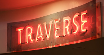 Red neon sign reading 'TRAVERSE'.