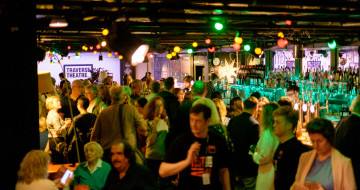 Traverse Bar Café is busy with people. Multi-Coloured lights hand from the ceiling and the square Traverse logo is visible in the background.