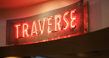 Neon sign reading 'TRAVERSE'.