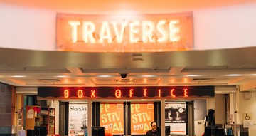 Red neon signs reading 'TRAVERSE' and 'BOX OFFICE'. Below them, a is a counter with four computers on top.