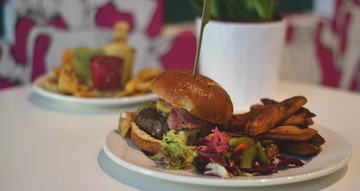 A burger with chips and salad