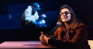 A woman wearing and winter coat and glasses is sitting at a table. She is speaking into a microphone.