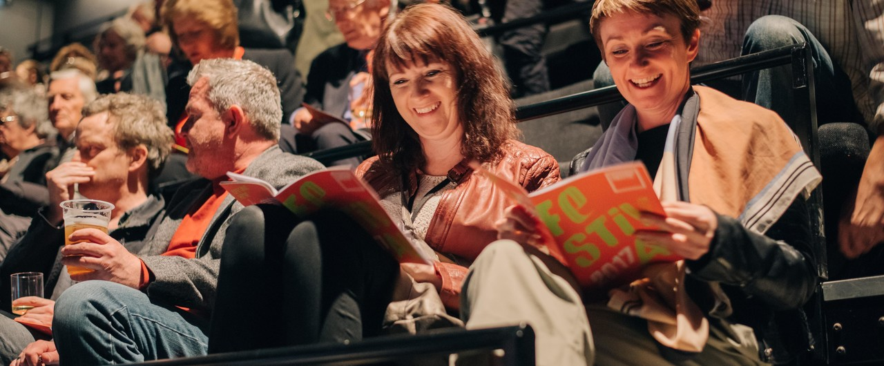 Taken in our Traverse 1 performance space. Two women are smiling and discussing the Traverse Festival brochure in their laps. People around them are chatting, drinking and looking at brochures.