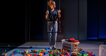 Production image. A woman stands holding on to a swing in front of her. At her feet is an ocean of children's toys and a basket of washing.