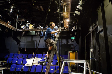 In our Traverse 2 performance space, a technician is up a ladder rigging lights.