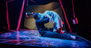 Production image. A woman bends over backwards to kiss a man who sits on the floor holding her waist.