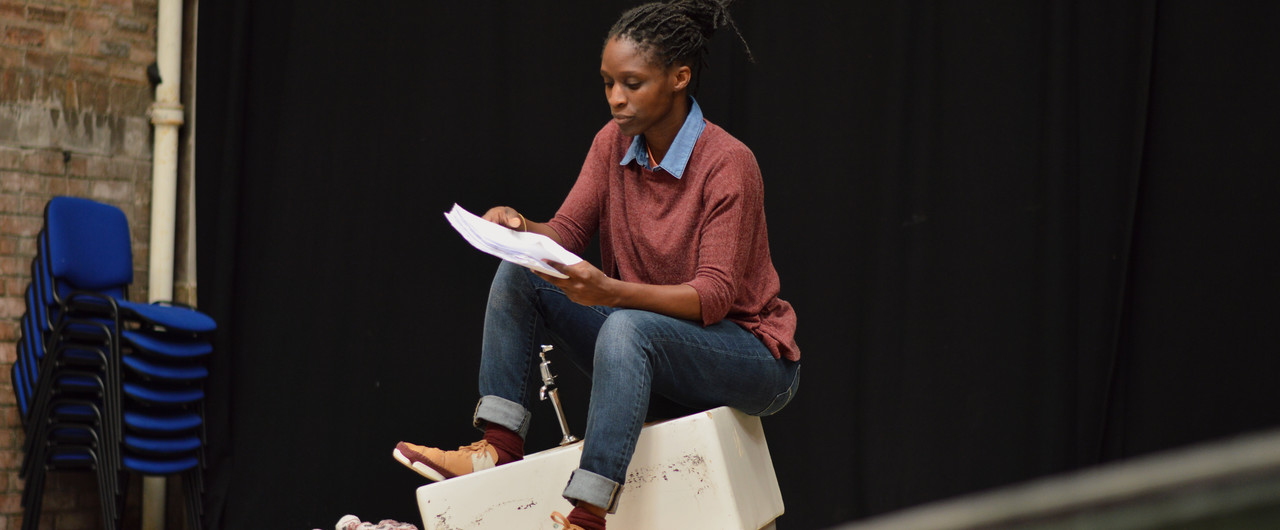 Photo taken during rehearsals for Meet Me At Dawn. A female actor sits on top of a bathroom sink reading a script. There is sand around her feet.