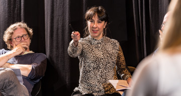 A woman wearing an animal print shirt and large hoop earrings points at the camera.