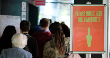 People queuing to get into a performance space. A sign reads 'Please queue for Traverse 2'.
