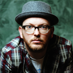 Associate Artist Tim Price is wearing glasses, a checked shirt and a grey felt hat.