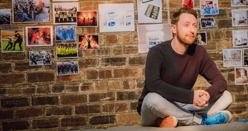Image taken during rehearsals for Girl in the Machine. A male actor sits crossed legged. On the exposed brick wall behind him, reference images cover the wall.