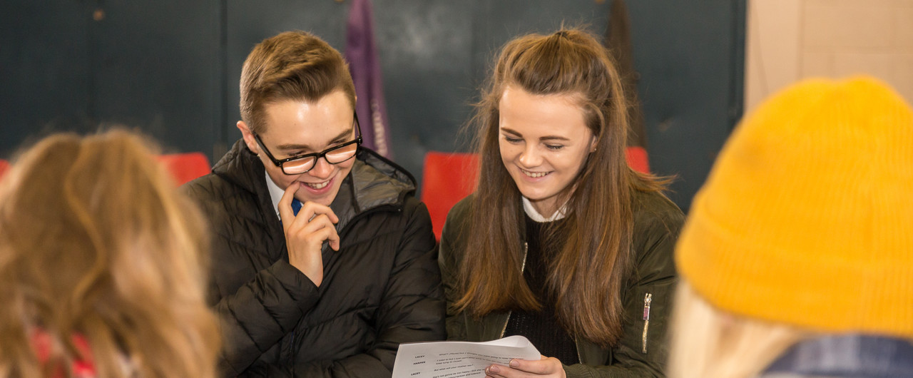 Two student are looking at a script. They are smiling.
