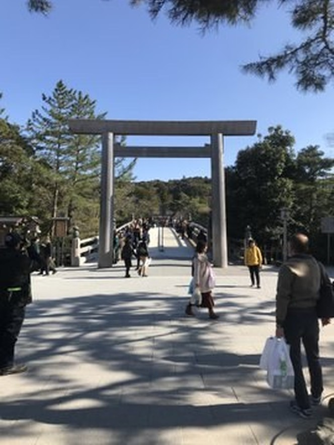 In the mid distance there is a large white wooden Shinto shrine gate.