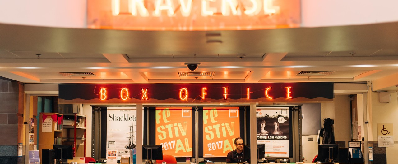 Traverse Theatre box office. Red neon signs read 'Traverse' and 'Box Office'. A man sits at a desk in front of four large photos.