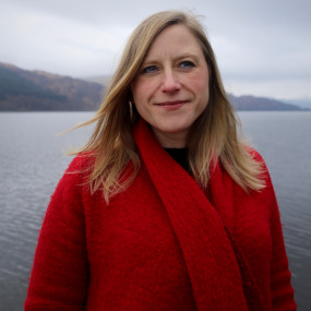 Frances Poet has long blonde hair. She is wearing a red coat and standing in front of a lake.