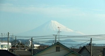 Behind a row of houses, Mount Fuji is just visible on the horizon.