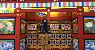 Andrew Thompson, a tall, dark haired and bearded man, stands in front of an elaborately painted doorway. The door are painted with vivid tiles with images of flowers.
