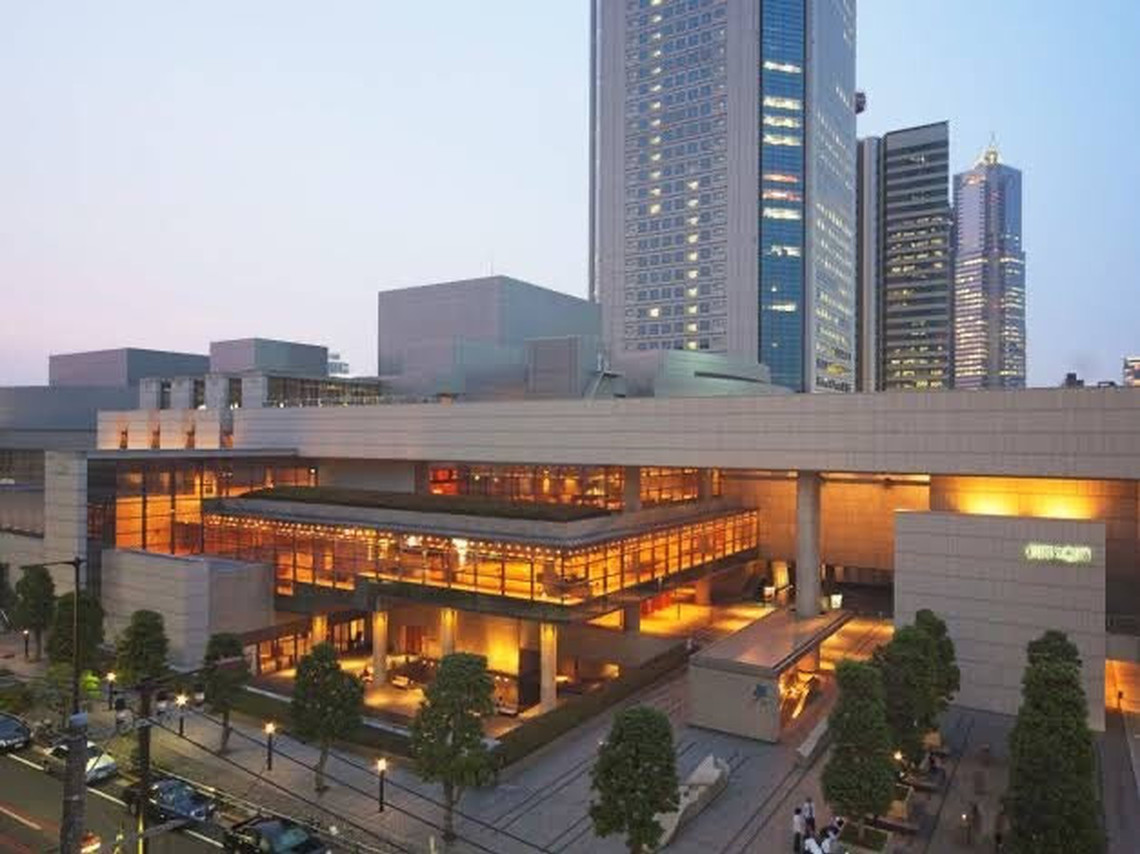The National Theatre of Japan: a large, rectangular, modern looking building made of white stone with four stories. It is fronted by an avenue of tall trees and lit by internal orange lights.