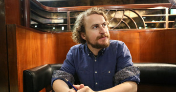 Gary McNair has shoulder-length curly blonde hair. He also has a short and neat moustache and bread. He sits in a booth, with his forearms resting on a table. He is wearing a shirt with the sleeves rolled up.
